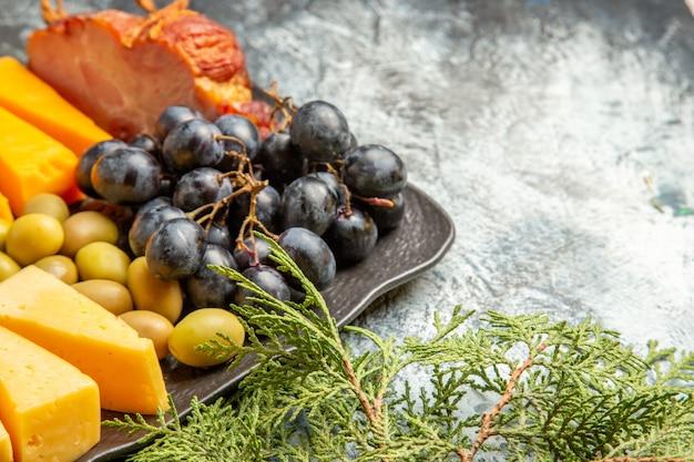 Meia dose do melhor lanche saboroso para vinho na bandeja marrom e galhos de pinheiro no fundo de gelo