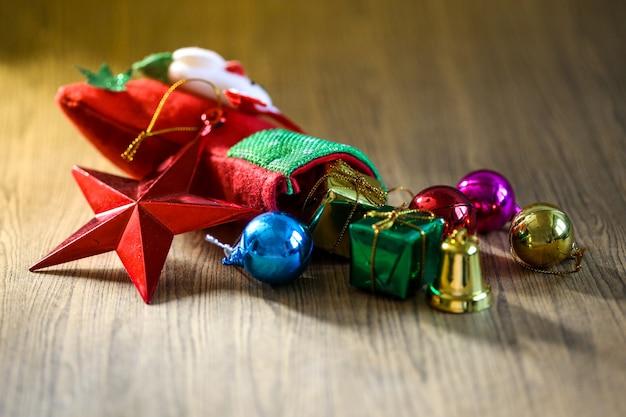 Meia e brinquedos da decoração do natal que penduram sobre o fundo de madeira