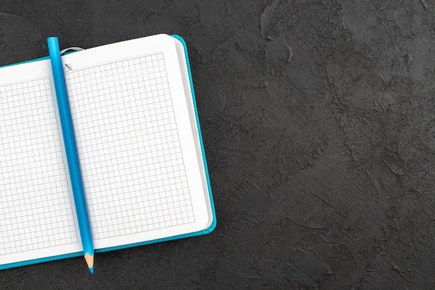 Meia foto de caderno azul aberto e caneta preta