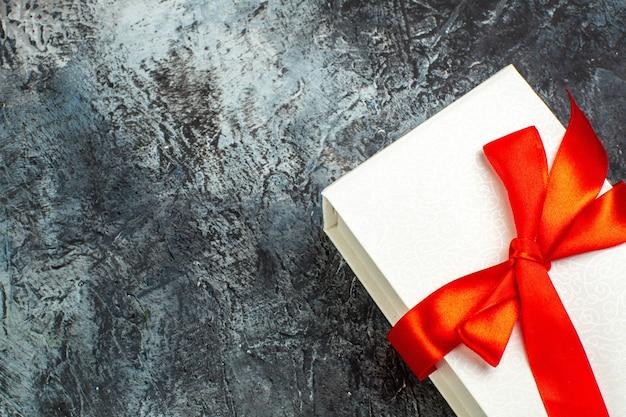 Meia foto de caixas de presente lindamente embaladas, amarradas com fita vermelha no lado direito no escuro