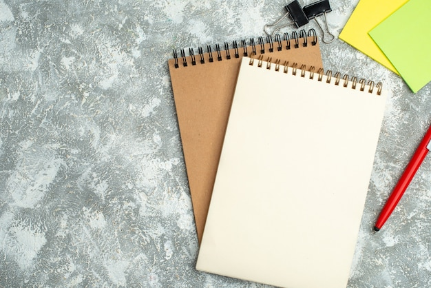 Meia foto de dois cadernos espirais kraft com canetas coloridas sobre fundo de gelo