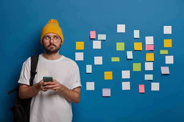 Meia foto de estudante pensativo usa óculos, chapéu e camiseta branca, tem boa produtividade, usa smartphone para aprender informações