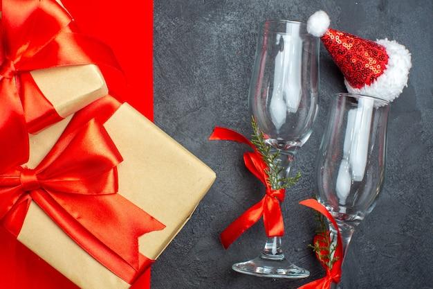 Meia foto de fundo de natal com taças de vidro com chapéu de papai noel e presentes com fita vermelha em forma de arco em fundo vermelho e preto