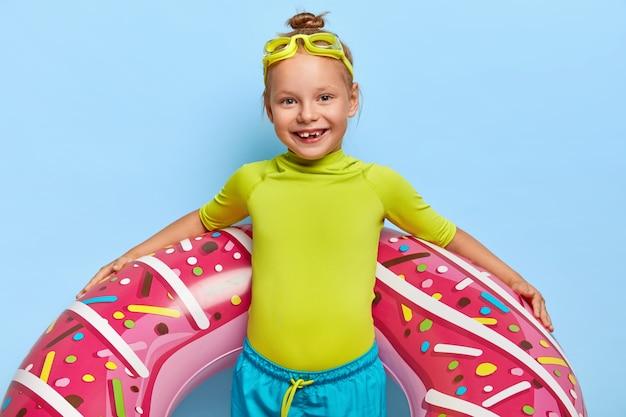 Meia foto de menina ruiva feliz com coque de cabelo, usa camiseta verde e shorts azuis, carrega uma piscina inflável, tem óculos de natação na cabeça, pronta para nadar no mar passa o verão com os pais