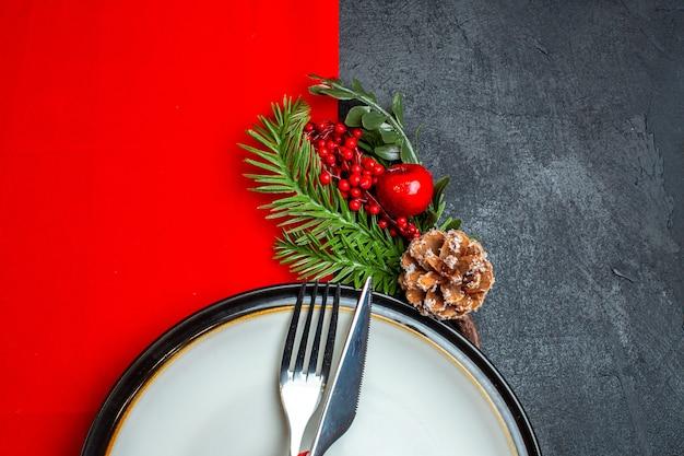 Meia foto de plano de fundo de natal com talheres com fita vermelha em um prato de jantar acessórios de decoração ramos de abeto em um guardanapo vermelho em uma mesa escura