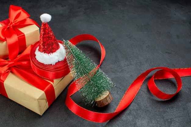 Meia foto de presentes bonitos com fita vermelha e chapéu de papai noel, árvore de natal na mesa escura