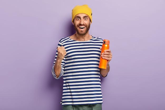 Meia foto de um turista masculino feliz comemora a viagem final, levanta o punho cerrado, segura o frasco laranja, tem expressão alegre, usa um chapéu amarelo e um macacão de marinheiro listrado, isolado sobre a parede roxa