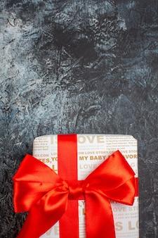 Meia foto de uma linda caixa de presente amarrada com uma fita vermelha em um fundo escuro de gelo