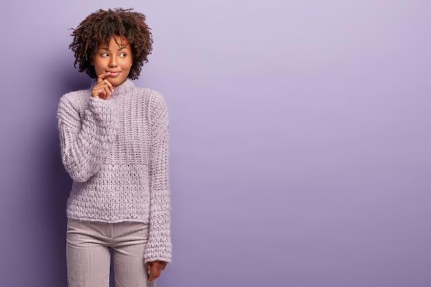 Meia foto de uma senhora afro-americana sorridente e pensativa olha de lado, usa um macacão de inverno quente e calças em um tom, pensa em fazer compras no fim de semana, o que comprar