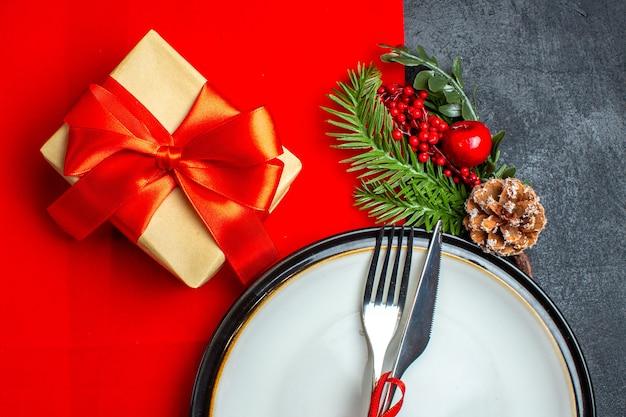 Meia foto do fundo de ano novo com talheres com fita vermelha em um prato de jantar acessórios de decoração ramos de abeto ao lado de um presente em um guardanapo vermelho