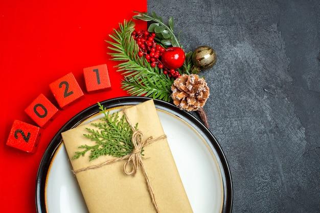 Meia foto do plano de fundo de ano novo com o presente no prato de jantar acessórios de decoração ramos de abeto e números em um guardanapo vermelho sobre uma mesa preta