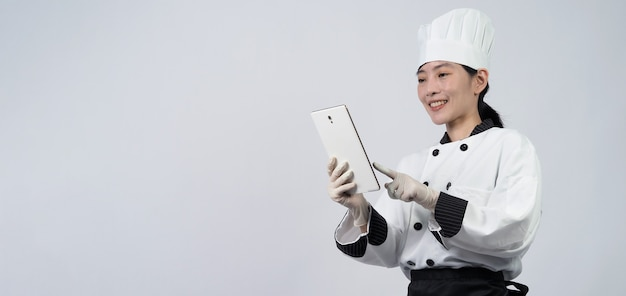 Meia-idade do chef mulher asiática segurando um smartphone ou tablet digital e recebeu o pedido da loja online ou do aplicativo do comerciante.