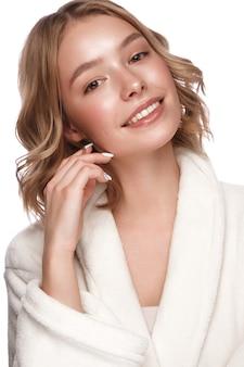 Meia jovem linda com um jaleco branco com pele limpa, fresca, posando na frente da câmera. rosto bonito. cuidados com a pele. foto tirada em estúdio em um fundo branco e isolado.