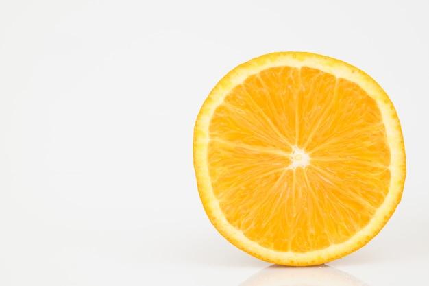 Meia laranja cortada em branco.