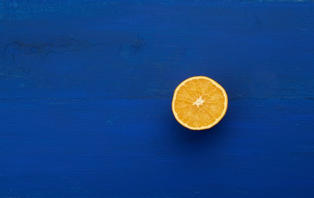 Meia laranja suculenta madura sobre um fundo azul escuro de madeira