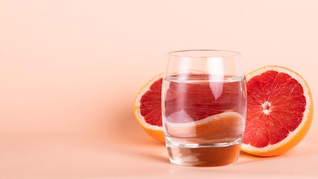 Meia laranja vermelha e vidro no arranjo de água