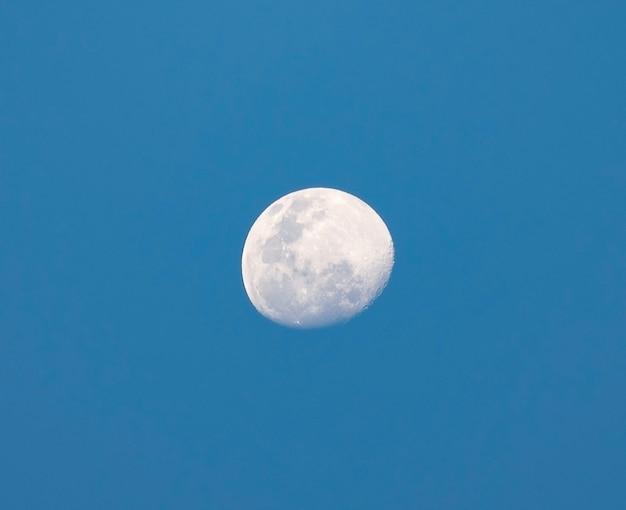 Meia lua durante o dia no fundo do céu azul