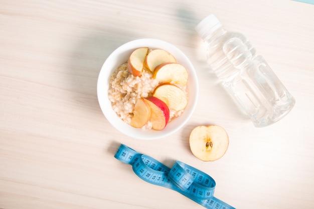 Meia maçã, garrafa de água, uma tigela de mingau de aveia fervido com maçã fatiada e uma fita métrica azul em uma mesa de madeira