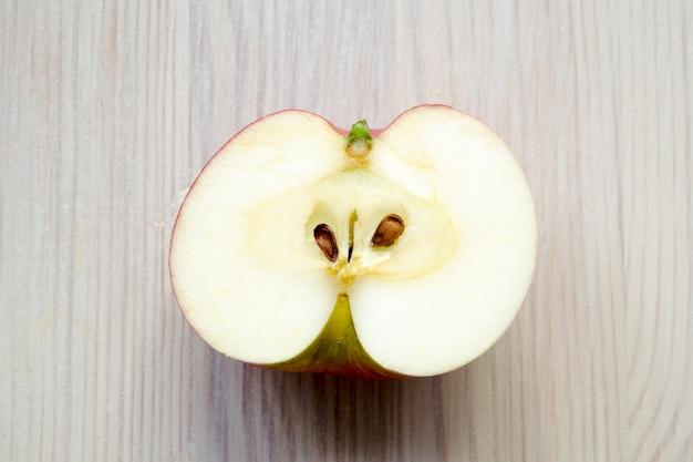 Meia maçã no fundo claro de madeira