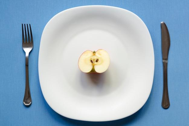 Meia maçã no prato branco com fundo de toalha de mesa azul