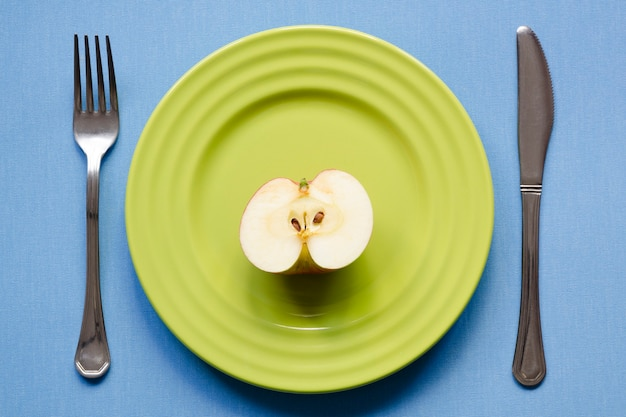 Meia maçã no prato verde com fundo azul