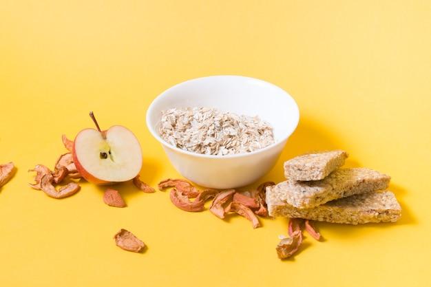 Meia maçã, uma tigela com aveia seca, maçãs secas e algumas barras de lanche em uma superfície amarela