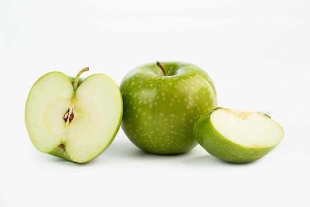 Meia maçã verde suculenta fresca de frutas meio corte e pedaços no chão branco