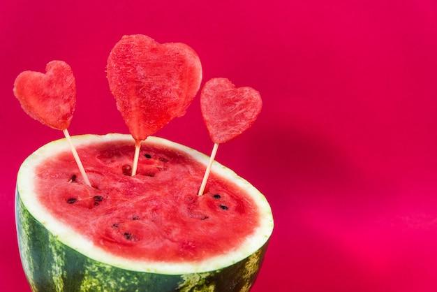 Meia melancia suculenta, decorada com corações decorativos em uma vara de madeira, isolada em um fundo vermelho