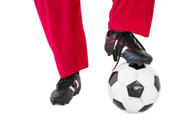 Meia metade das pernas de santa com botas de futebol e futebol