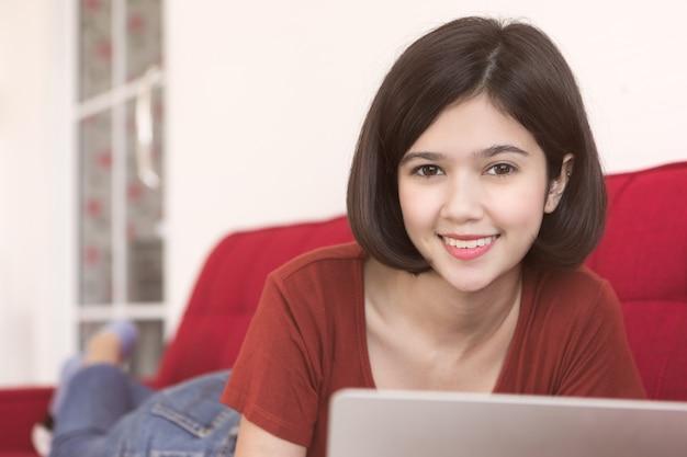 Meia raça tailandesa-alemã linda garota deitada na cama no quarto e usando o laptop notebook para trabalhar em casa com uma sensação confortável e relaxada.