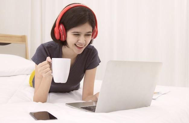 Meia raça tailandesa-alemã linda garota segurando a xícara de café branca deitada na cama no quarto e usando o trabalho do computador notebook laptop de casa com sentimento de felicidade.