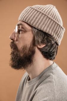Meia retrato de um homem branco de óculos e chapéu isolado sobre uma parede amarela clara. bigode e barba. conceito de emoções humanas, expressão facial, anúncio, moda. copie o espaço