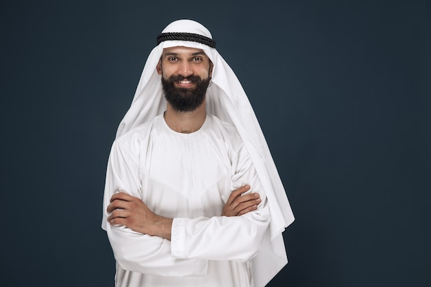 Meia retrato do empresário da arábia saudita em fundo azul escuro do estúdio. jovem modelo masculino em pé e sorrindo. conceito de negócios, finanças, expressão facial, emoções humanas.