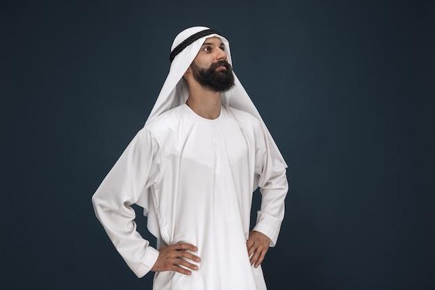 Meia retrato do empresário saudita árabe em fundo azul escuro do estúdio. jovem modelo masculino em pé e sorrindo. conceito de negócios, finanças, expressão facial, emoções humanas.