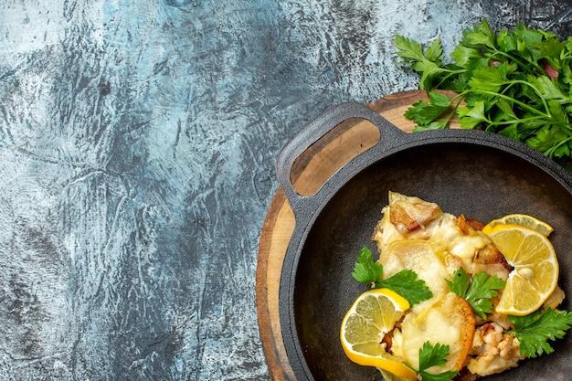 Meia superior vista de peixe frito na panela na tábua de madeira salsa na mesa cinza cópia local