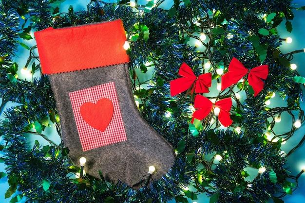Meia vermelha com coração e presente entre luzes de natal e enfeites coloridos no fundo