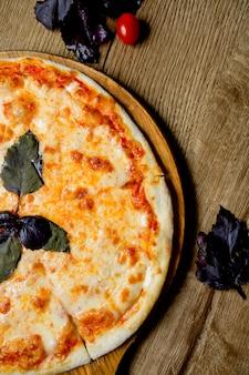 Meia vista da pizza margarita, guarnecida com manjericão