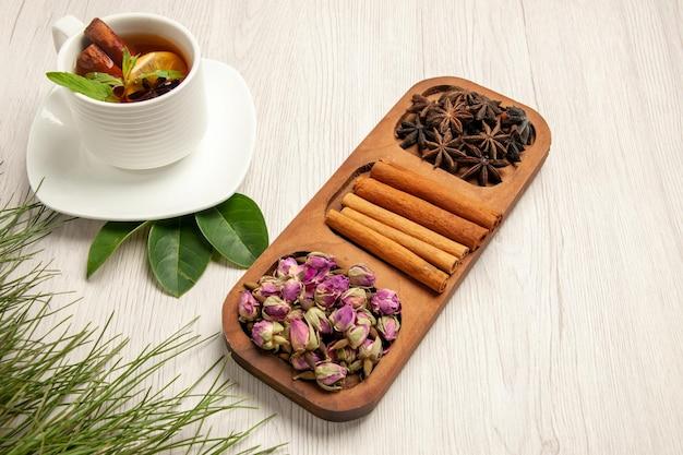 Meia vista de cima xícara de chá com canela e flores na mesa branca, cor de chá, sabor flor