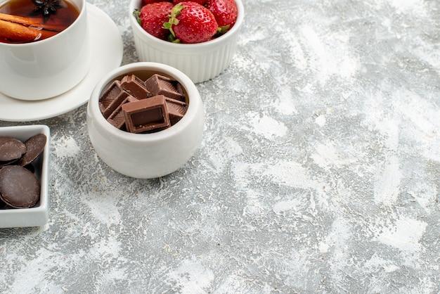 Meia vista inferior tigelas com morangos e chocolates e chá de sementes de anis de canela no canto superior esquerdo do fundo cinza-esbranquiçado
