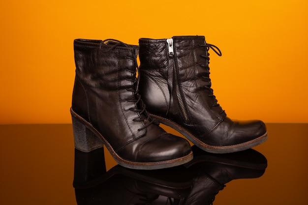 Meias botas pretas com salto alto na mesa de vidro preto e fundo amarelo. conceito de moda e design, compras.