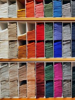 Meias coloridas empilhadas na prateleira na loja de roupas