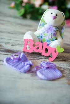 Meias de bebê de malha roxa com a inscrição de uma criança e uma lebre de brinquedo em um fundo de madeira.