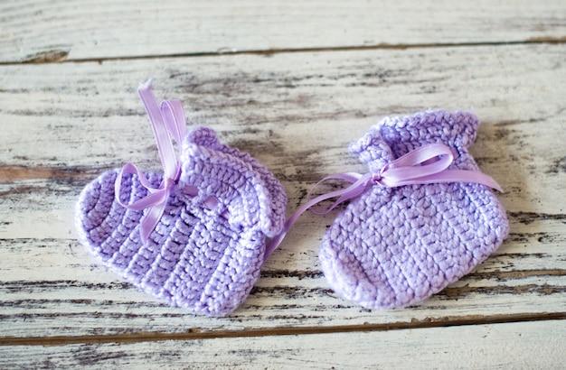 Meias de crochê roxas para bebês com fundo de madeira