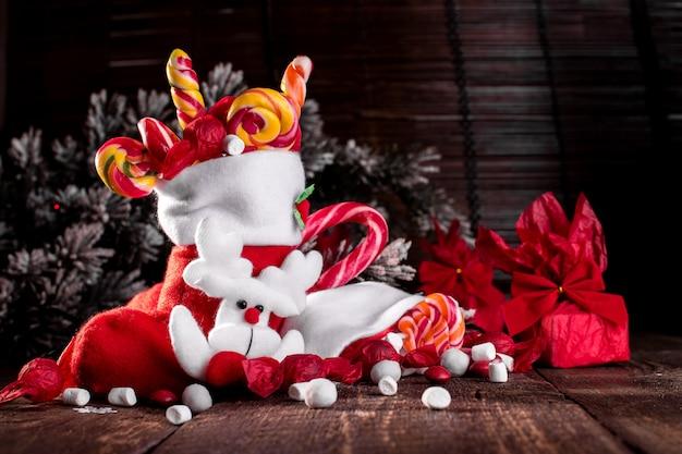 Meias de natal cheias de doces e guloseimas em fundo de madeira.