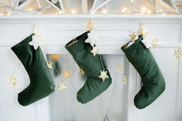 Meias de natal para os presentes do papai noel estão penduradas sobre a lareira da casa