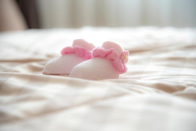 Meias do bebê recém-nascido na cama em tom morno