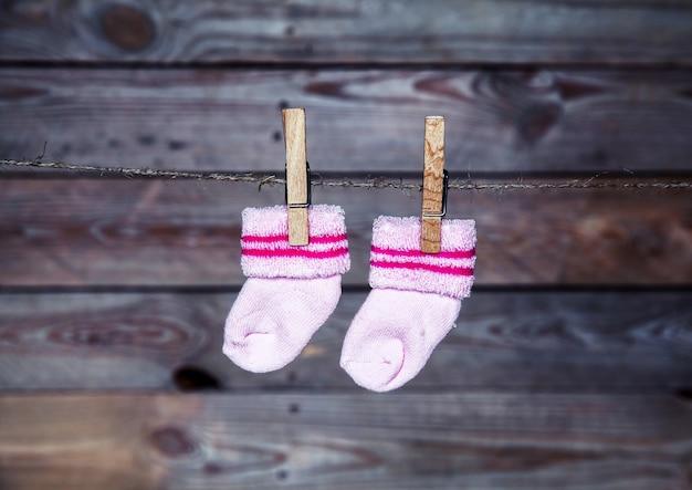 Meias rosa penduradas na parede de madeira do prendedor de roupa