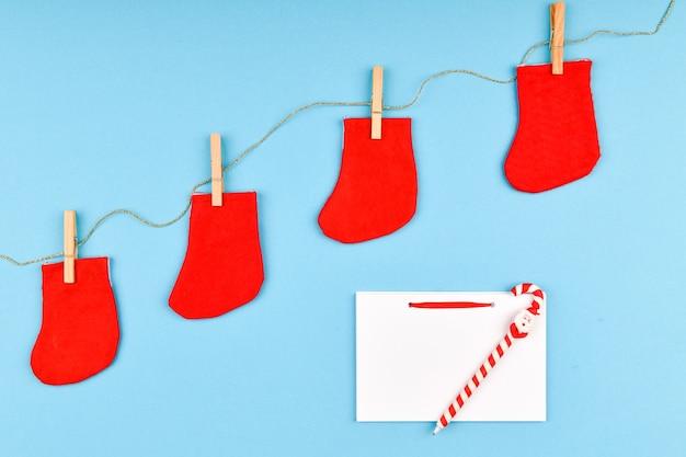 Meias vermelhas em um prendedor de roupa. em um espaço azul. um caderno em branco com um monte. vista de cima. pendurado no varal com prendedores de roupa em um espaço azul. conceito de ano novo.