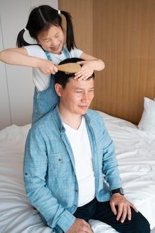 Meidum baleado na criança escovando o cabelo do pai