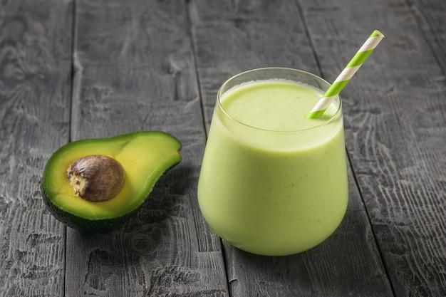 Meio abacate e um copo de vidro com um smoothie e um tubo de coquetel em uma mesa de madeira. produto de fitness. nutrição esportiva dietética.
